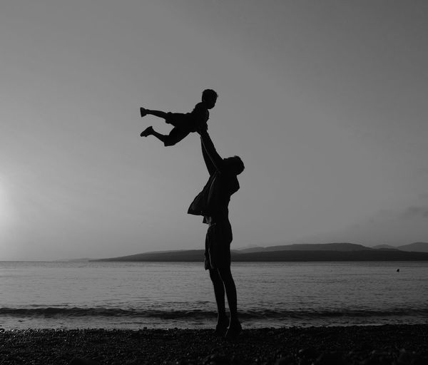 Silhouette Father Lifting Son At Beach Against Sky