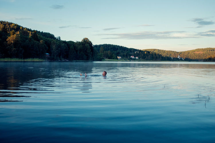 Young man floating in beautiful blue lake Beard Beauty In Nature Blue Water Day Enjoying Life Floating On Water Holiday Lake Male Nature One Person Outdoors People Red House Reflection Relaxing Sky Summer Sweden Swimming Tranquility Water