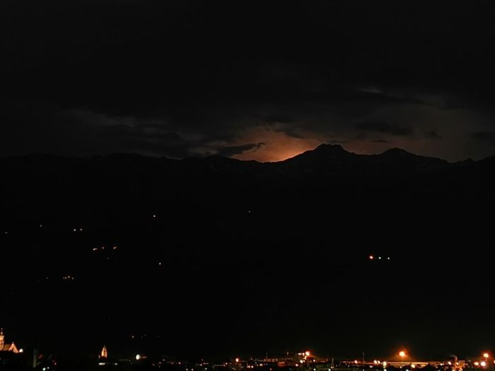 Low angle view of illuminated mountain against sky at night