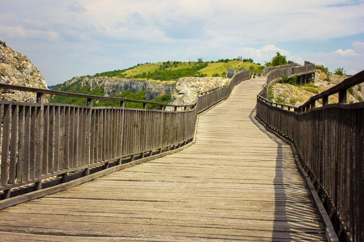 Boardwalk leading towards footbridge against sky
