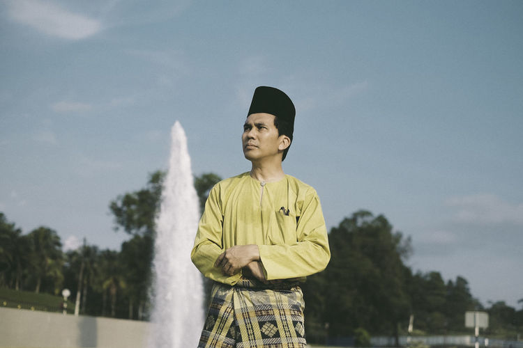 Man with traditional clothing against sky