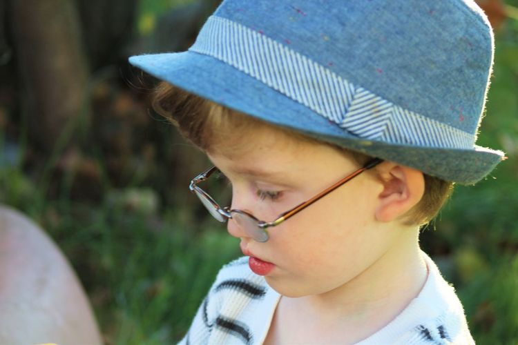 Close-up of boy wearing eyeglasses and hat