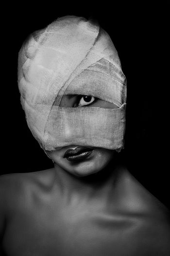 Close-Up Portrait Of Topless Young Woman Face Wrapped In Bandage Against Black Background