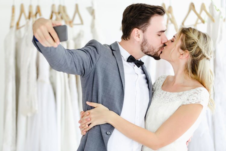 Couple kissing while taking selfie in bridal shop