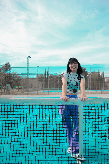 Portrait of woman standing at tennis court against sky