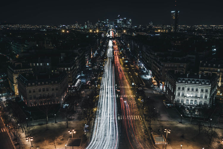 High angle view of light trails in illuminated city at night