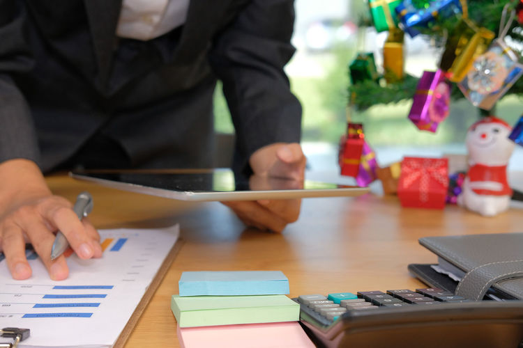 Midsection of businessman working on table during christmas