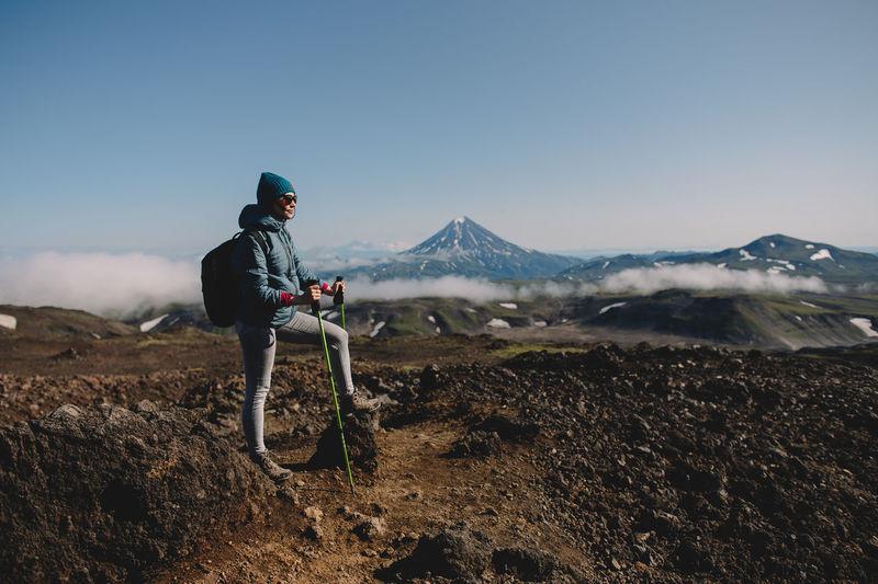 Woman standing on landscape against mountain range