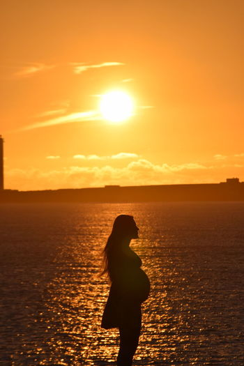 Silhouette Pregnant Woman Standing At Beach During Sunset