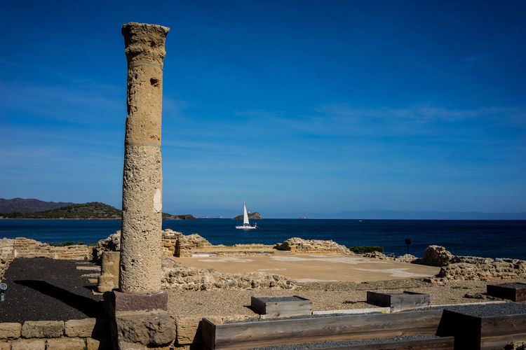 Archaeological site of Nora (Sardinia) Ruins Ancient Architecture Ancient Civilization Beach Beauty In Nature Blue Column Day Horizon Over Water Nature Nautical Vessel No People Outdoors Ruins Architecture Sailboat Scenics Sea Sky Sunlight Travel Destinations Water My Best Travel Photo