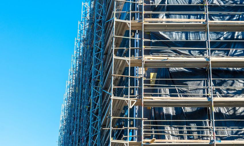 Low angle view of scaffolding on building against clear blue sky