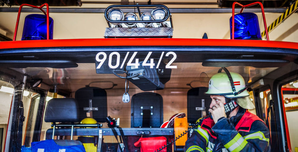 Firefighter Using Phone In Fire Engine