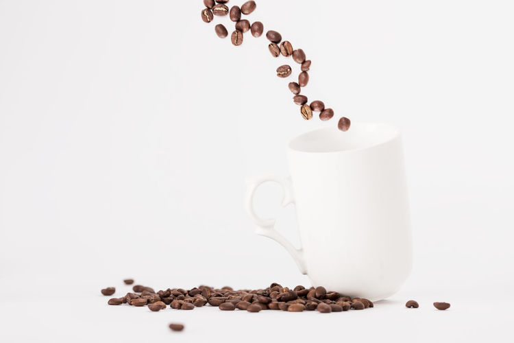 White Coffee Cup With Fresh Coffee Beans Fly Out of a Cup on a White Background Concept with Copy Space White Background Food And Drink Studio Shot Drink Indoors  Roasted Coffee Bean Still Life Refreshment Coffee - Drink Coffee Food Cup Freshness No People Large Group Of Objects Mug Coffee Cup Copy Space Close-up Caffeine