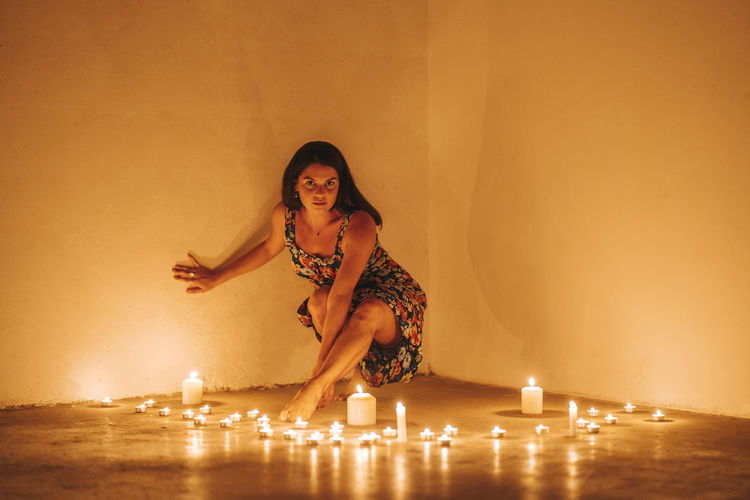 Young woman sitting against illuminated wall