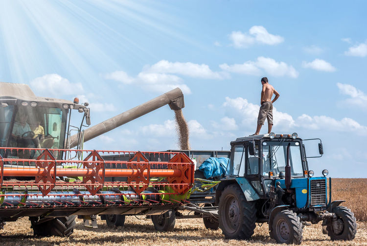 harvester Agricultural Machinery Agriculture Cloud - Sky Combine Harvester Construction Site Day Field Land Vehicle Outdoors Real People Sky Tractor Transportation