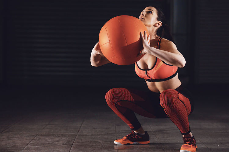 Full Length Of Woman Holding Medicine Ball And Squatting In Gym