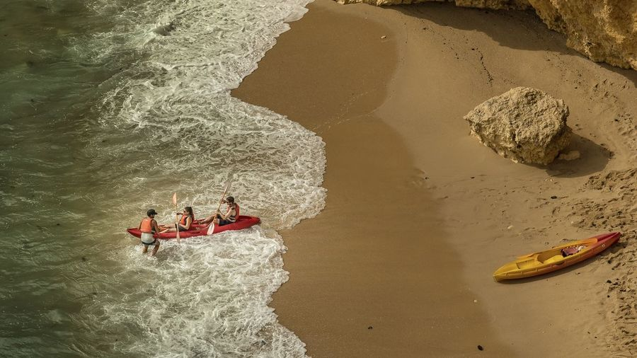 High Angle View Of Father With Children Canoeing In Sea