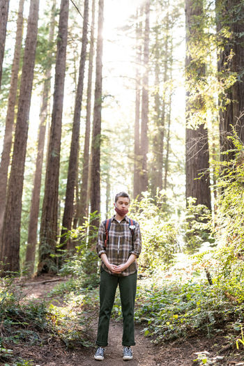 Full length of man standing amidst trees in forest