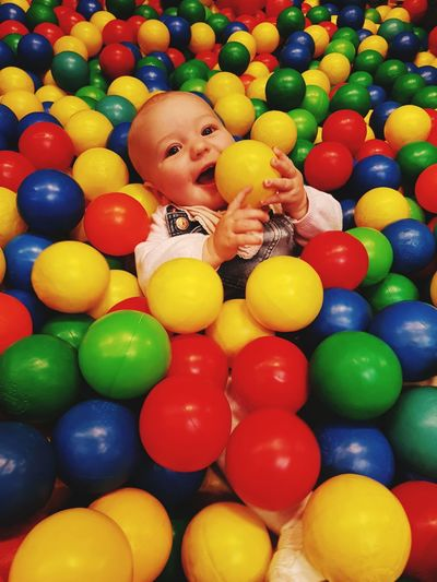 High angle view of cute baby girl colorful ball pool