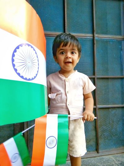 Smiling boy holding flags outside house