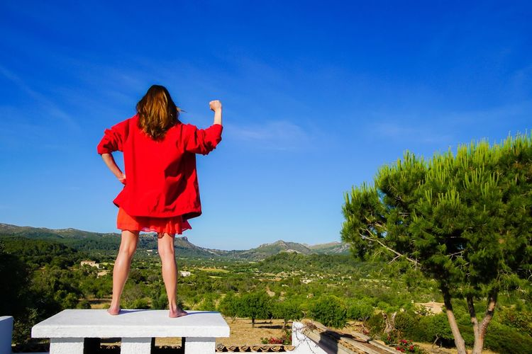 Rear View Of Woman Gesturing While Standing On Built Structure Against Blue Sky