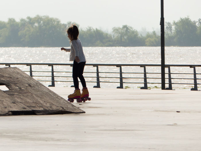 Girl roller skating on footpath against lake