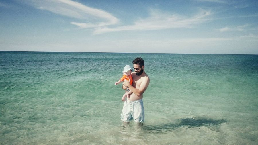 Man Standing In Sea With Baby
