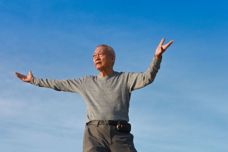 Low section of man standing against blue sky