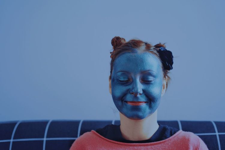 Close-up of young woman with beauty mask against blue wall