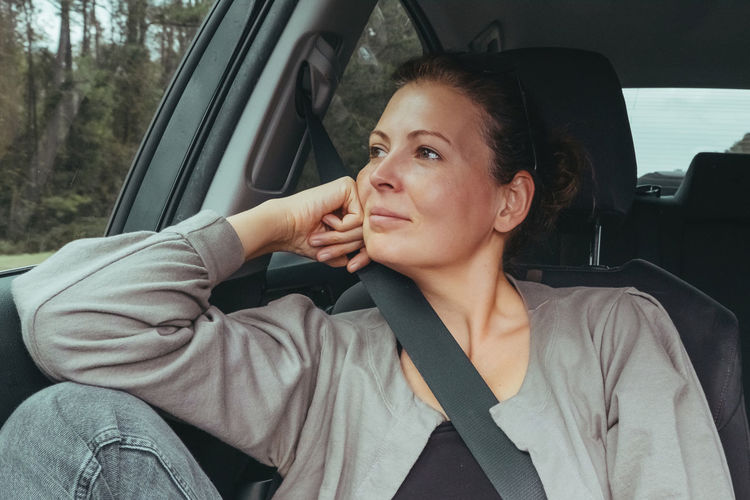 Woman looking away while sitting on car