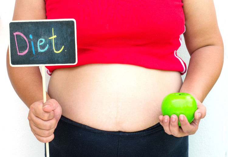 Midsection of woman holding blackboard and granny smith apple while standing against white background