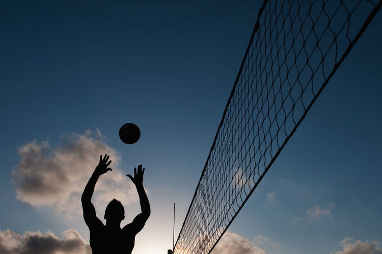 Silhouette man playing volley ball against sky