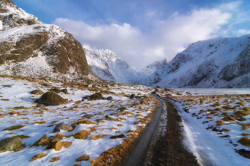Road amidst snow covered mountains against sky norway