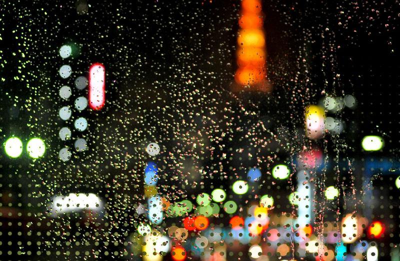 COLOURFUL DEFOCUSED LIGHTS AT NIGHT SEEN THROUGH WET WINDOW