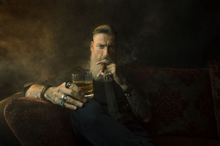 Portrait Of Hipster Man Smoking Cigar While Holding Beer Glass Against Wall