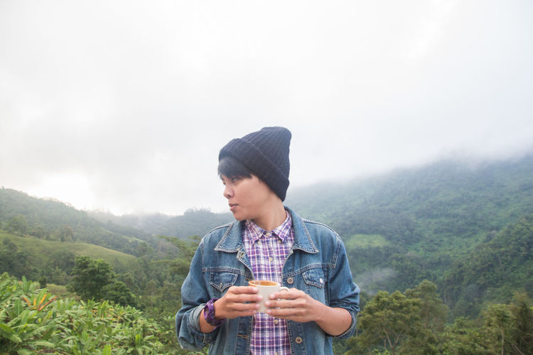 Young man holding ice cream against mountains