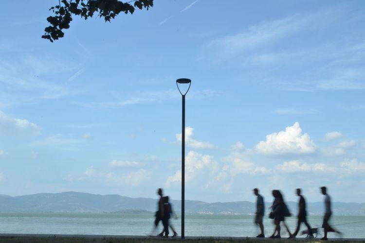 People standing on street against sky
