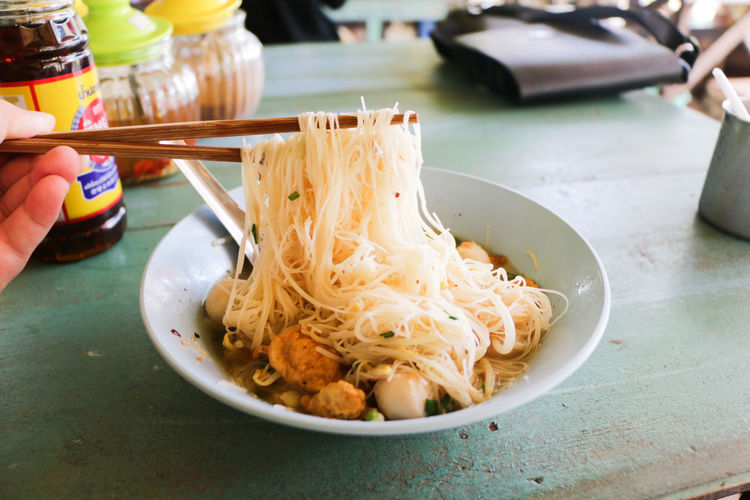Close-up of hand holding noodles in bowl on table