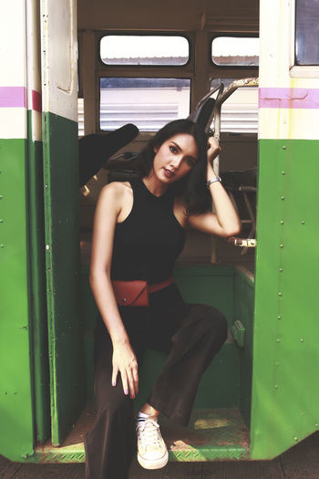 Portrait of young woman sitting on train