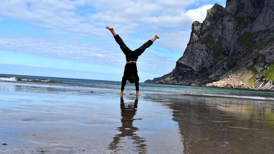 Full length of man with arms raised on beach