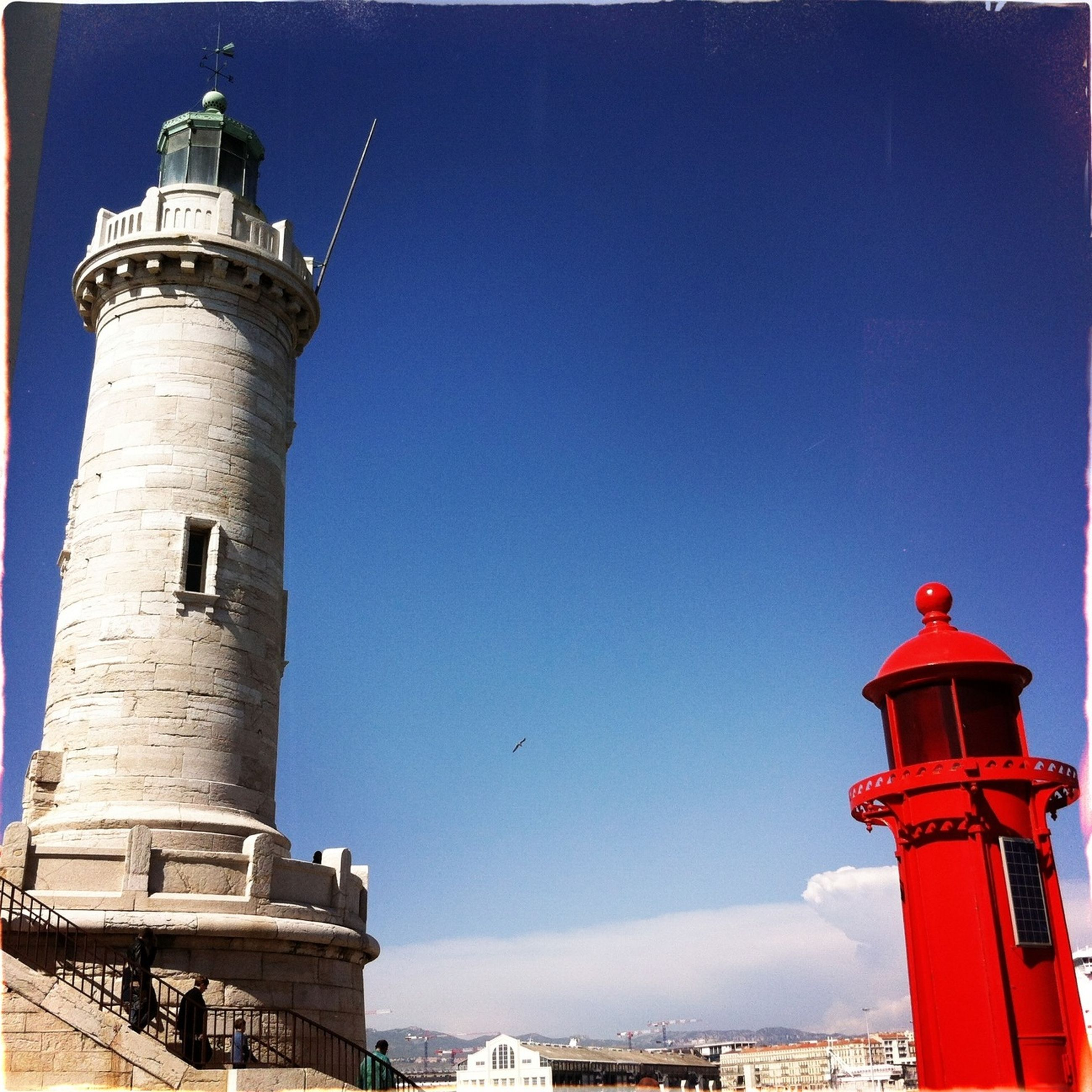 architecture, built structure, building exterior, lighthouse, clear sky, low angle view, guidance, red, tower, blue, copy space, protection, direction, safety, security, outdoors, day, no people, travel destinations, sky