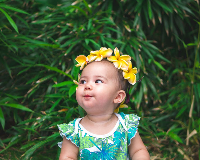 Baby girl wearing yellow frangipanis while looking away against plants