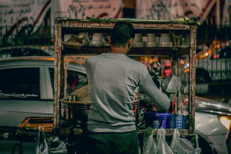 Rear view of man working at market