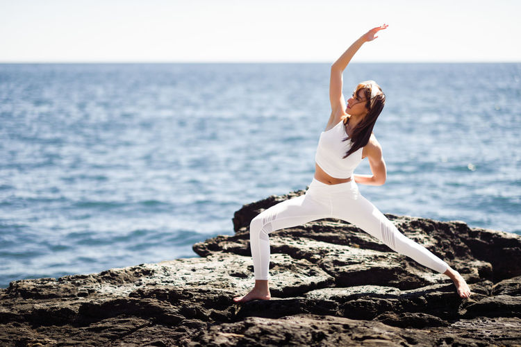 Young woman doing yoga in the beach. Female wearing white sport clothes in warrior 2 figure with defocused sea background. Females Nature Woman Yoga Yoga Pose Young Beach Girl Sea Young Adult Young Women