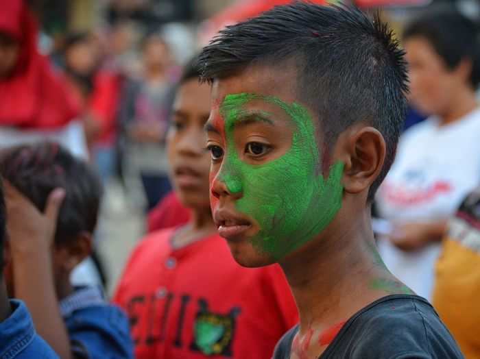 Close-up of boy with green face paint during celebration