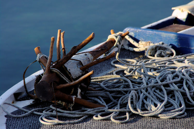 Wooden anchor tied by rope on boat over lake