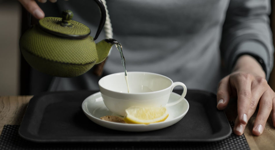 Midsection of man pouring tea in cup