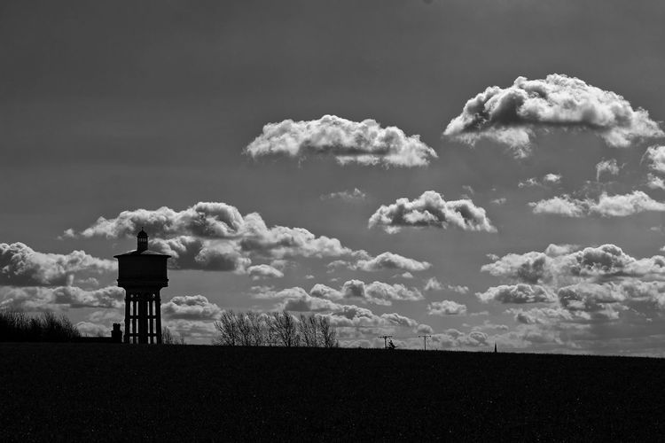 Scenic view of water tower on land against sky