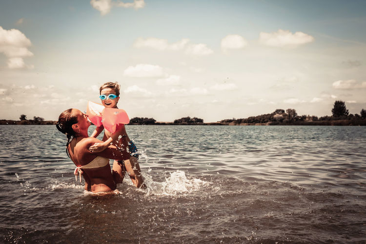 Playful mother and son having fun in water during summer day.