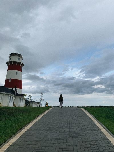 Rear view of man walking on footpath by lighthouse against sky